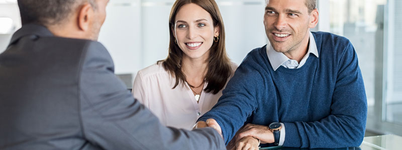 young couple meeting and shaking hands with mortgage broker