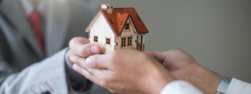Two people holding small model of house in their hands