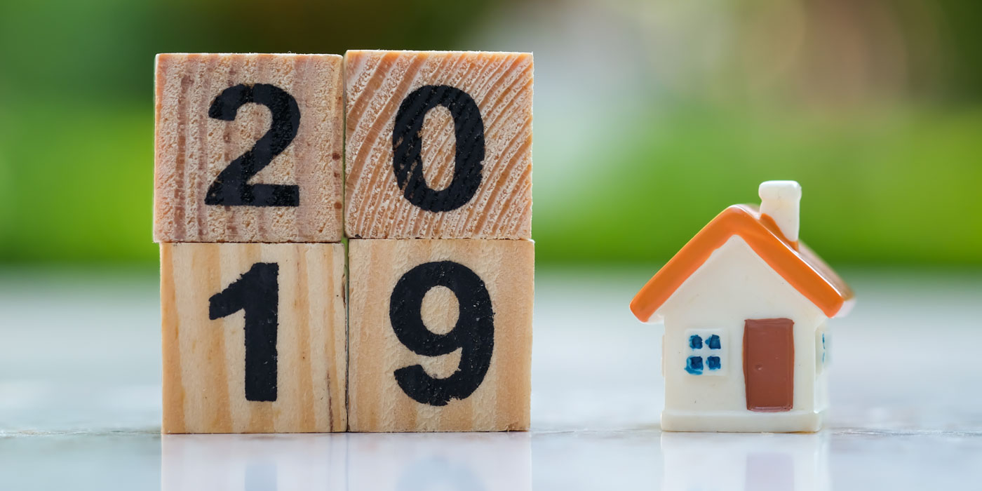 Wooden blocks with year 2019 on them, small toy house to the right