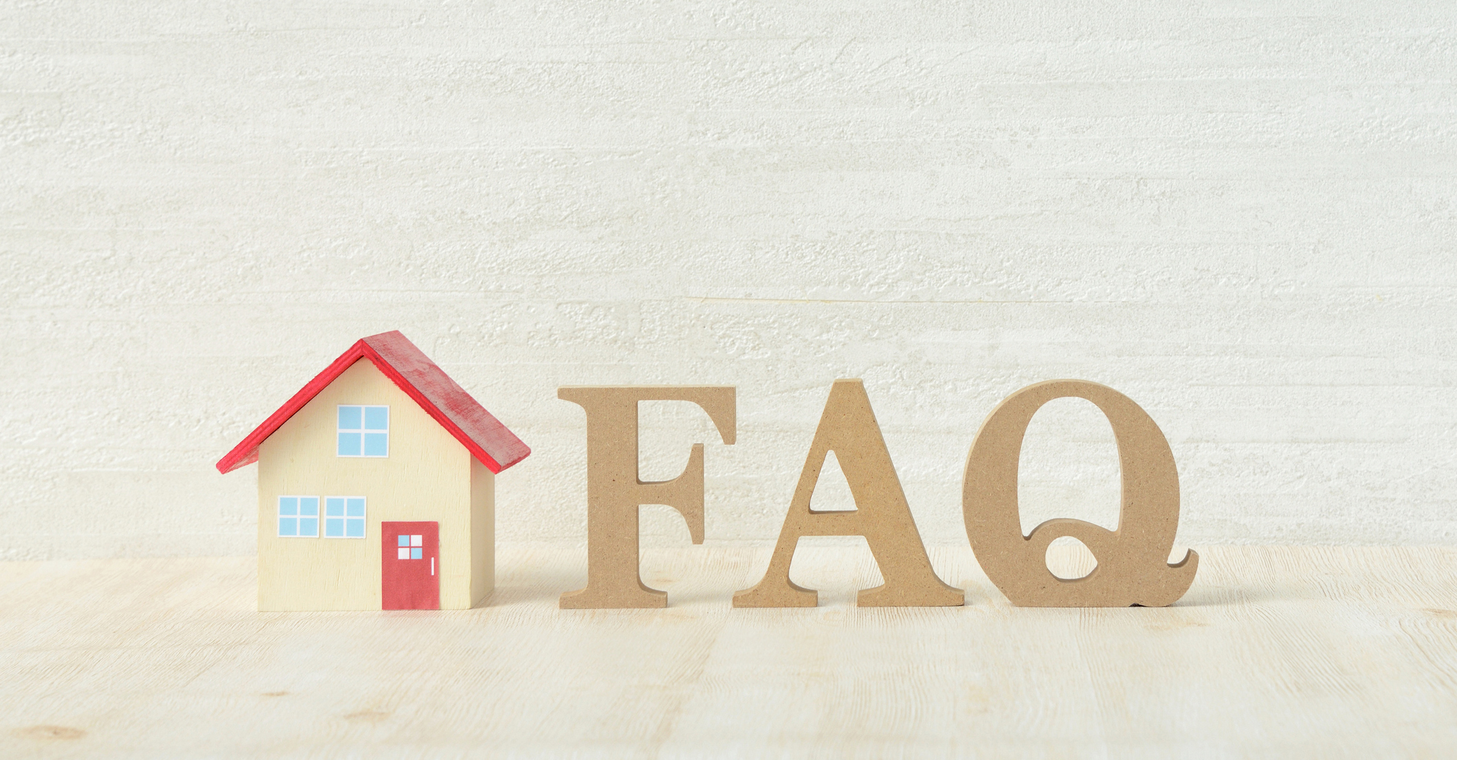 Small toy home next to the letters FAQ